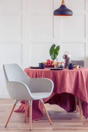 Elegant dining room table covered with ginger tablecloth in bright living room interior with stylish chairs Stock Photo - 129344184