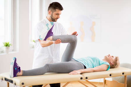 Middle age woman with knee injury lying on physiotherapy table during session with young handsome doctor