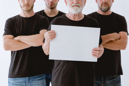 Man in black holding the piece of paper in front of him