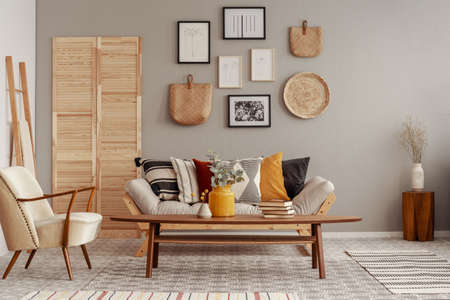 Trendy creme colored armchair in Scandinavian living room interior with gallery of posters on beige wall 写真素材