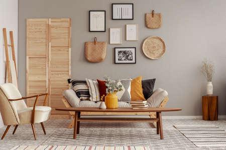 Sillón de color crema de moda en el interior de la sala de estar escandinava con galería de carteles en la pared beige