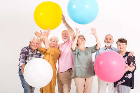 Older friends having fun with the balloons at the party