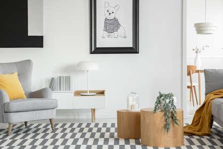 Affiche noir et blanc de chien sur le mur de l'intérieur du salon à la mode avec deux tables basses en bois avec des fleurs