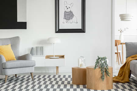 Black and white poster of dog on the wall of fashionable living room interior with two wooden coffee tables with flowers