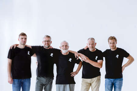 Group of men wearing black with white ribbons on t-shirts