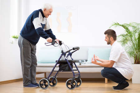 Elderly grandfather with walker trying to walk again and helpful male nurse supporting him