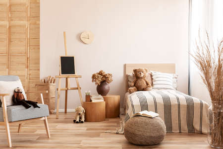 Teddy bear on single wooden bed in natural kid's bedroom Archivio Fotografico