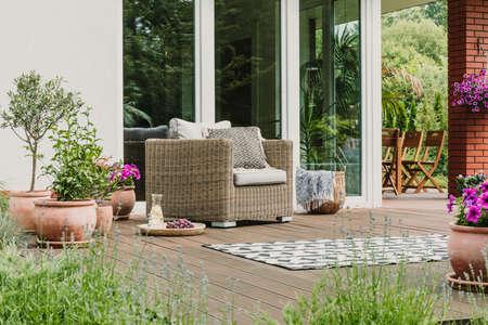Cómodo sillón de mimbre con almohadas en la terraza de madera de la casa suburbana de moda