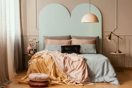 Literie bleu pastel, rose et orange sur lit double dans un intérieur chic de chambre