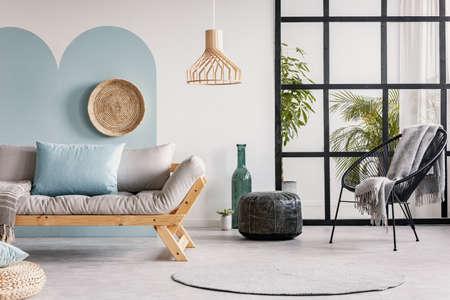 Urban jungle in bright white and blue living room interior with scandinavian futon sofa