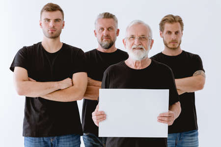 Men in black from different generations holding white board
