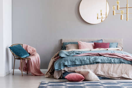 Pastel pink, beige and blue bedding on king size bed in trendy bedroom interior 免版税图像