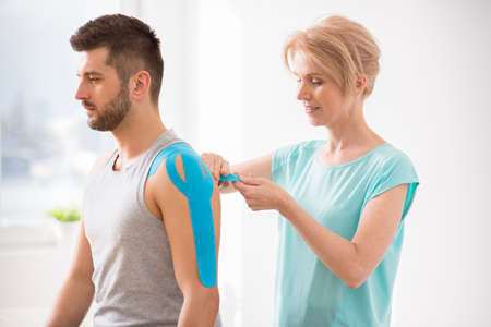 Physiotherapist covering selected fragments of young mans body with special structure patches during kinesiotaping therapy