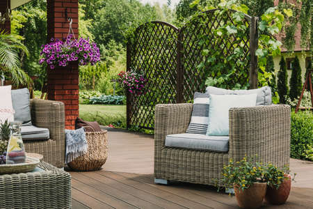 Comfy wicker armchair with pillows on wooden terrace of trendy suburban home 스톡 콘텐츠 - 129348493