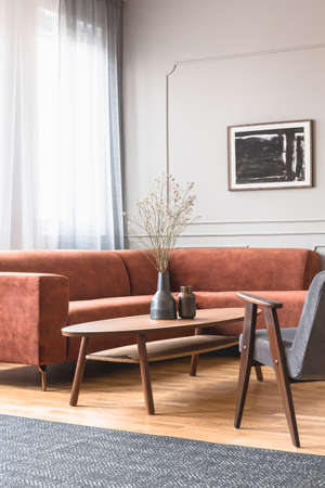 Trendy vintage armchair in stylish scandinavian living room interior with grey wall
