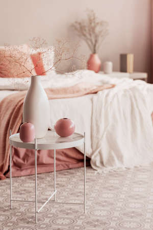 Big white vase with dry flowers next to two pastel pink vases on white industrial coffee table