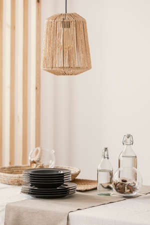 Close-up of stylish rattan lamp above table Stockfoto