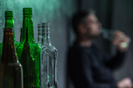 Close-up on empty bottles and blurred person drinking alcohol in the background