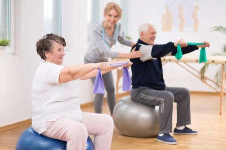 Anciano y mujer haciendo ejercicio sobre pelotas de gimnasia durante la sesión de fisioterapia en el hospital