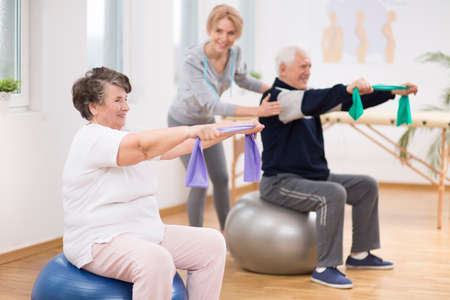 Elderly man and woman exercising on gymnastic balls during physiotherapy session at hospital Foto de archivo - 129864181