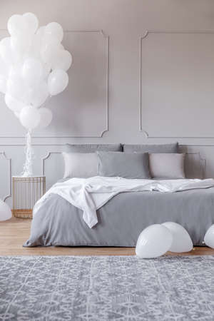 Copy space on the empty grey wall of contemporary bedroom with king size bed and bunch of white balloons above golden nightstand