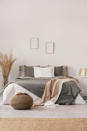 White and beige blankets on grey duvet on comfortable bed in bright bedroom interior Фото со стока