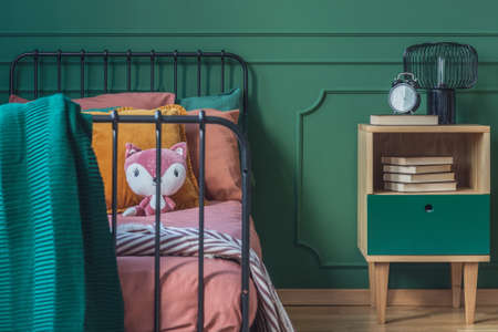 Closeup of single metal bed with orange bedding and fox toy Фото со стока