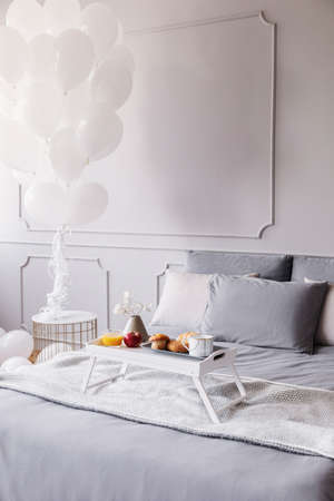 Birthday breakfast on white wooden trey on large bed with grey sheets and blanket, bunch of white balloons above nightstand, copy space on the empty wall