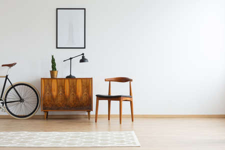 Bright living room interior with bike, vintage cupboard, poster on wall and carpet on floor in real photo Imagens