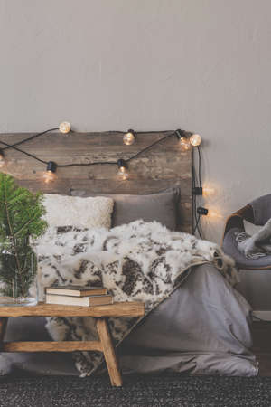 Christmas tree in glass vase next to books on wooden bench in the foot of a warm king size bed with wooden headboard