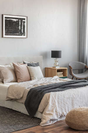 Trendy bedroom with comfortable king size bed in modern flat, real photo