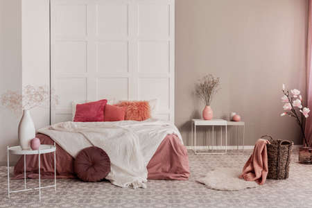Amaranth pillow and dirty orange bedding on king size bed in fashionable bedroom interior