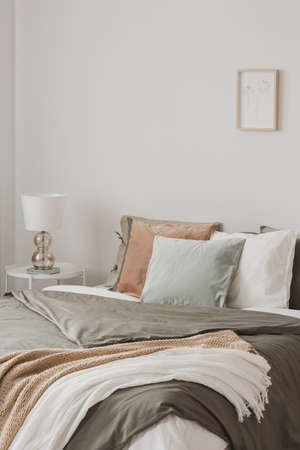 Colorful pillows in king size bed with duvet and blankets in hygge inspired bedroom Фото со стока
