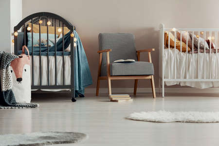 Stylish vintage armchair in the middle of cute baby room for twins Фото со стока