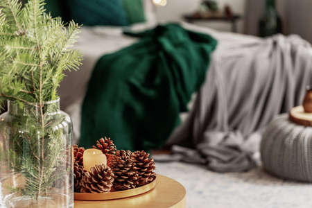 Spruce candle and cone on small wooden table in grey and emerald green bedroom interior Reklamní fotografie