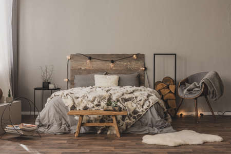 Copy space on empty grey wall of stylish bedroom interior with wooden accents and king size bed Фото со стока