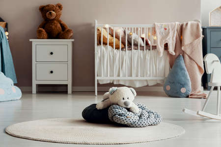 White teddy bear on dotted pillow on the floor of trendy baby bedroom