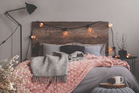 Grey and pastel pink blanket on grey bedding of fashionable bedroom with rustic design Фото со стока