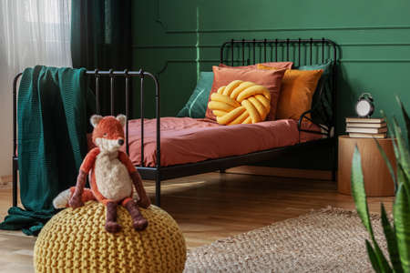 Fox toy on yellow pouf in small bedroom with metal bed with knot pillow