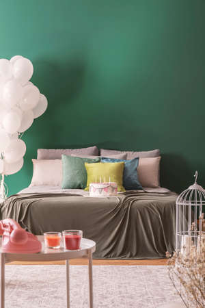 Colorful pillows and birthday cake with candles on king size bed in lovely bedroom, copy space on the empty wall Фото со стока