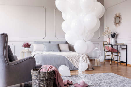 Bunch of white balloons in the middle of classy grey bedroom with elegant dresser with golden mirror, copy space on the empty wall