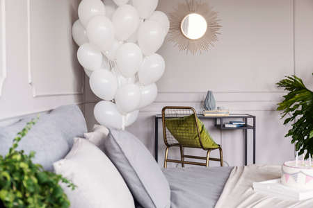 Olive green pillow on fancy golden armchair in chic bedroom with bunch of white balloons, copy space on the empty wall Фото со стока