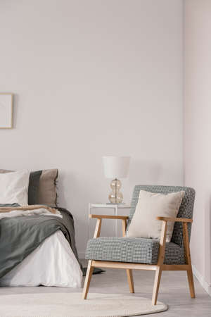 Retro armchair with white pillow next to cozy king size bed with grey bedding in fashionable bedroom interior Фото со стока