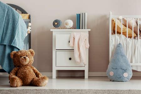 Brown teddy bear on the wooden floor of scandinavian baby bedroom interior