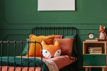 Orange pillow on single bed in dark green teenager bedroom