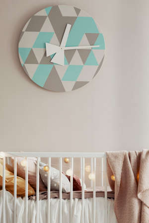 Stylish clock above wooden crib in beige baby room Фото со стока