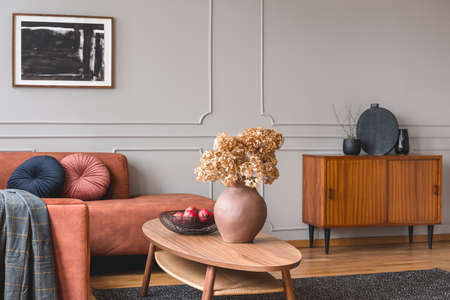 Retro wooden cabinet with black vases in the corner of classy grey living room interior with ginger sofa