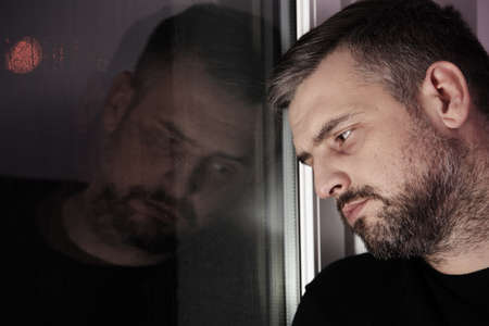Sad and lonely man with alcoholism problem looking through window