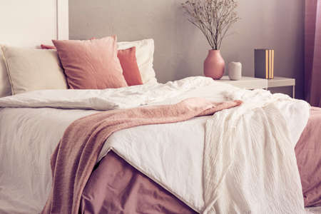 King size bed with pastel pink and white bedding in trendy bedroom interior