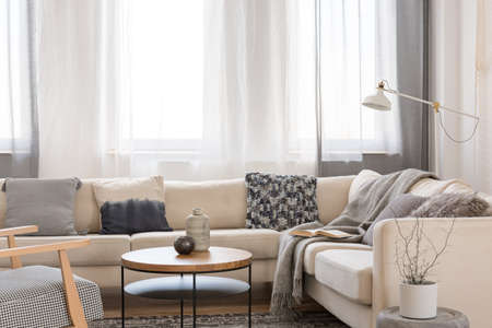 Beige comfortable corner sofa with grey pillows in elegant living room interior with white wall Фото со стока